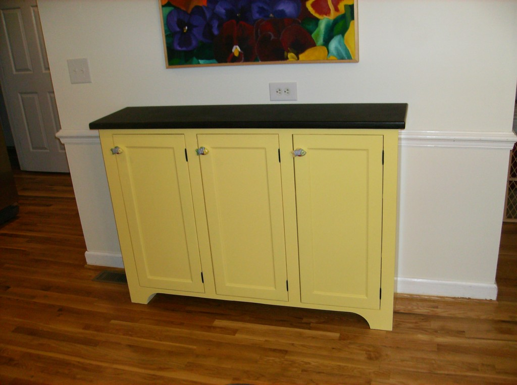 Reused an old upper cabinet and built new doors and furniture feet with a granite top to be used as a serving bar.